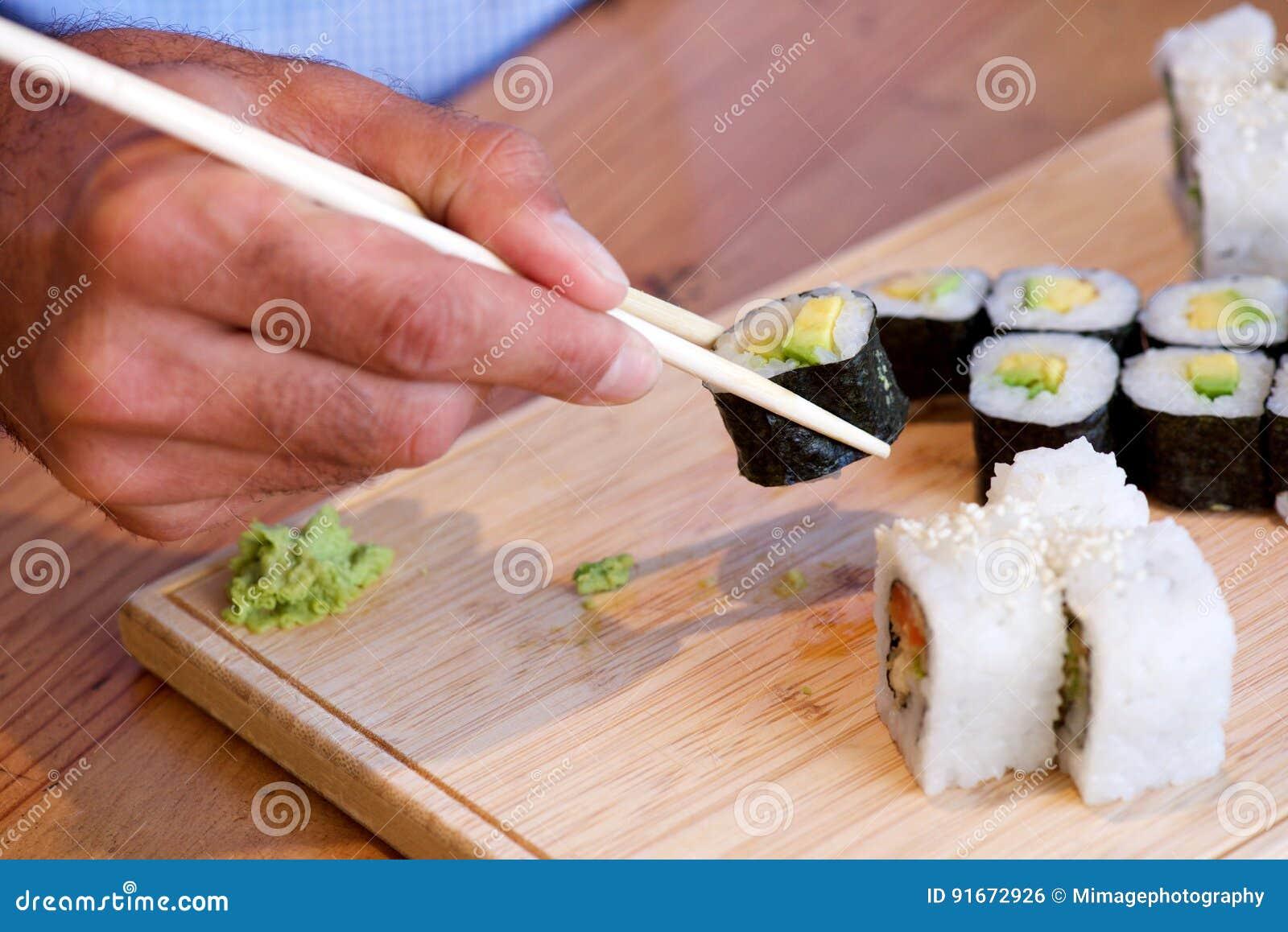 male hands holding chopsticks and eating sushi stock photo. Black Bedroom Furniture Sets. Home Design Ideas