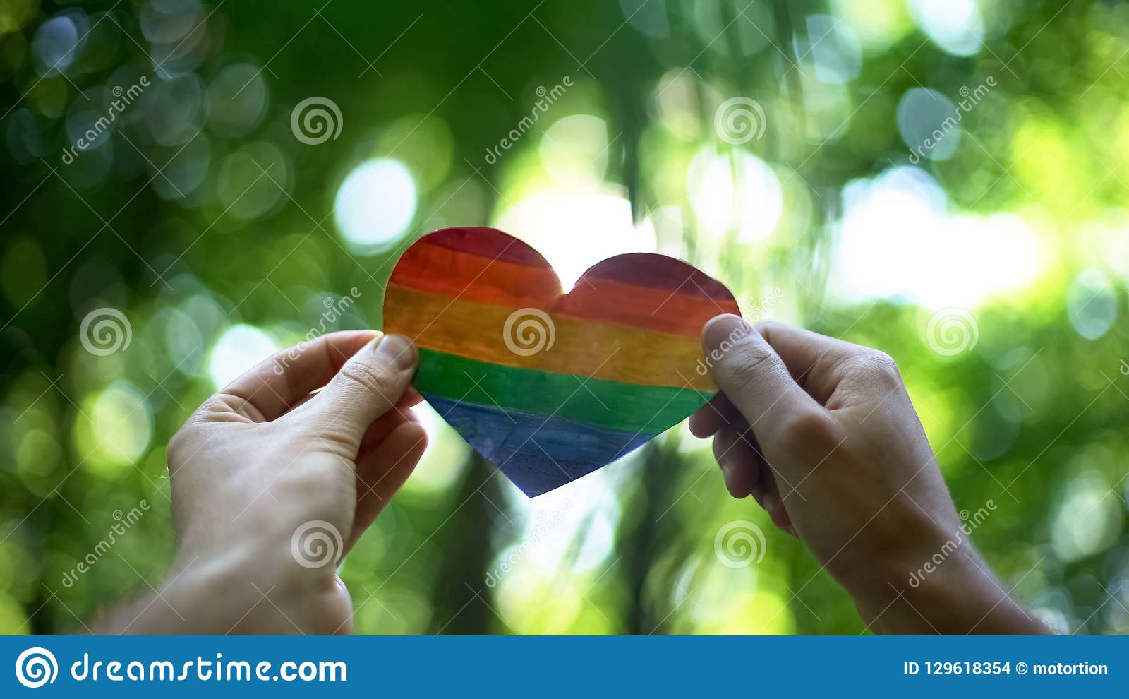 Male hands holding rainbow heart, global recognition of same-sex marriage