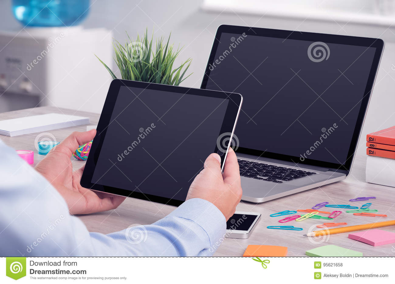 Male hands using ipad digital tablet pc and macbook laptop on the office desk