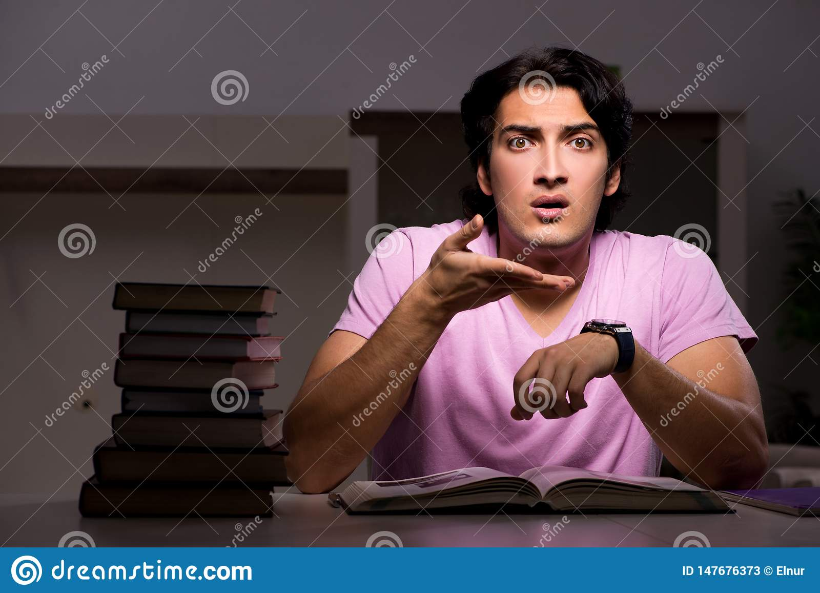 The male handsome student preparing for exams late at home