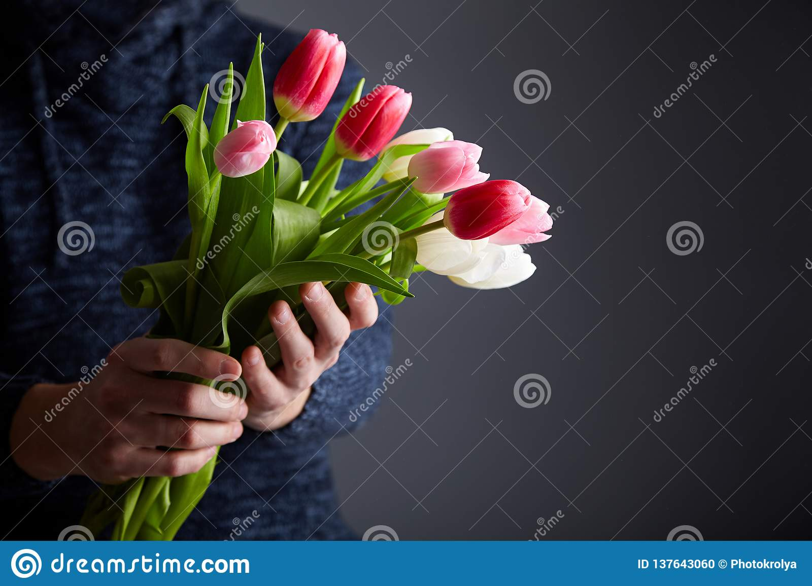 A Man holding bunch of tulips