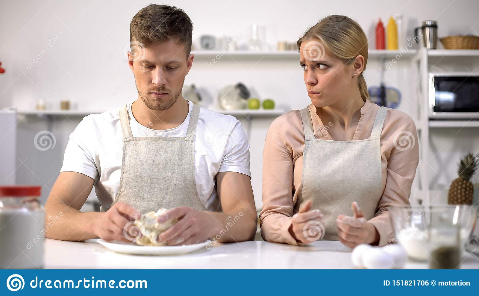 Male holding raw dough, wife looking awkwardly on husband, bad cook, problem