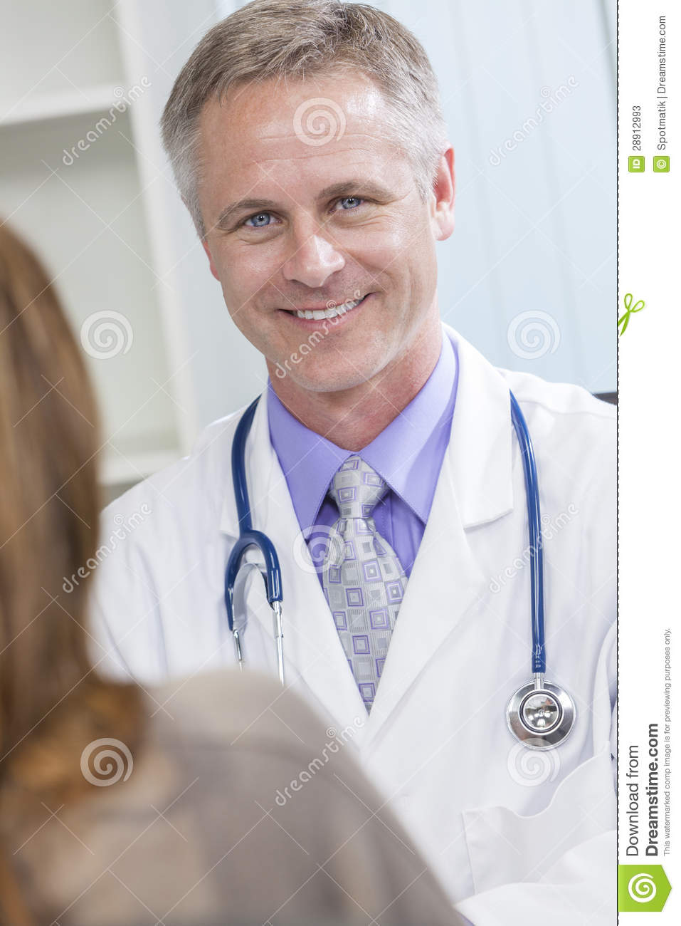 Male medical doctor talking to a female patient in a hospital office.