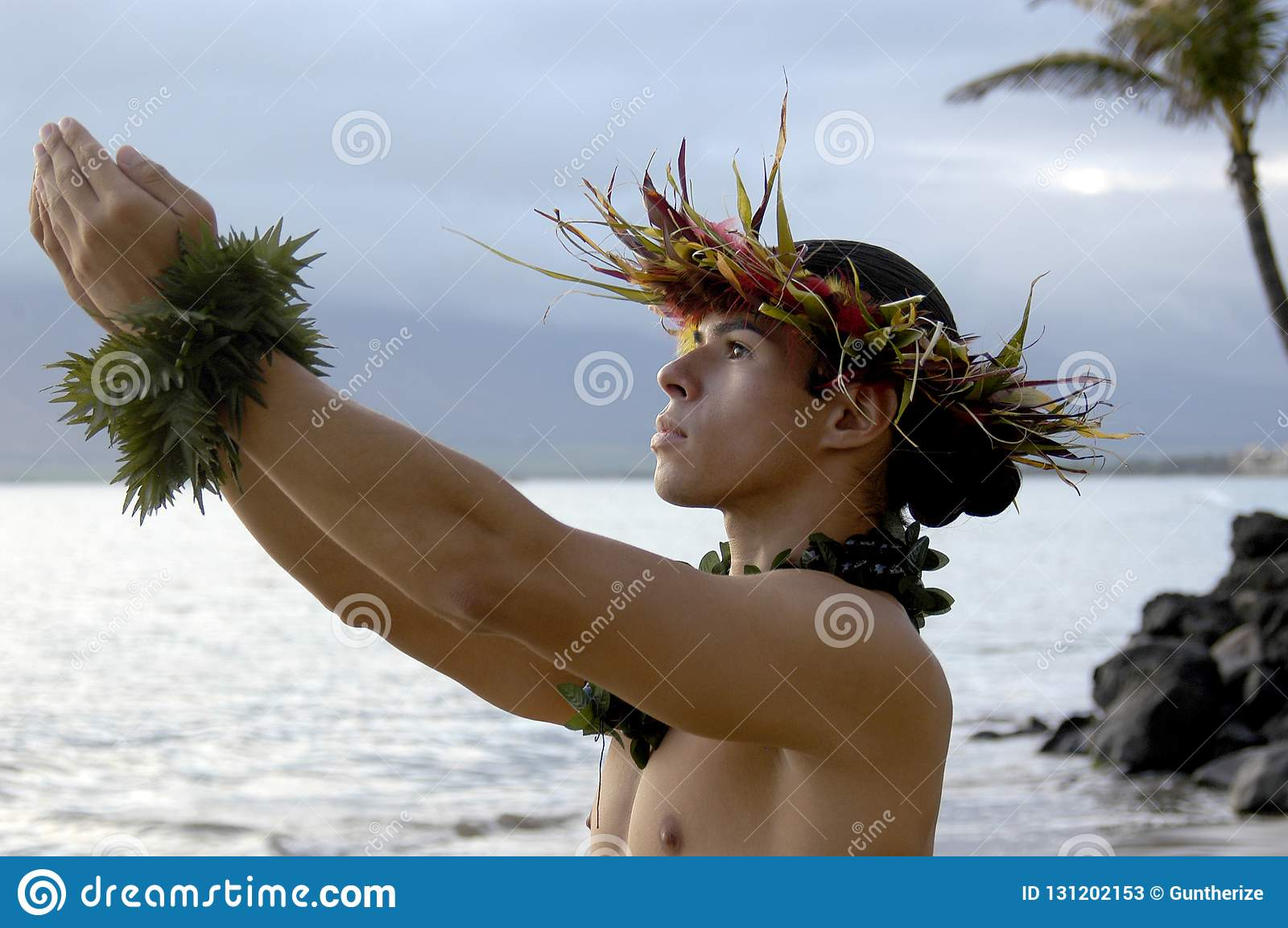 Male hula dancer praying and gesturing gifts to the heavens.