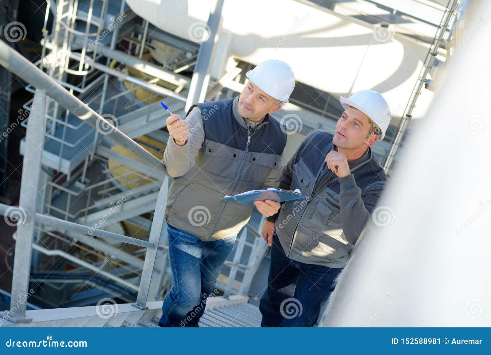 Male industrial factory maintenance workers talking