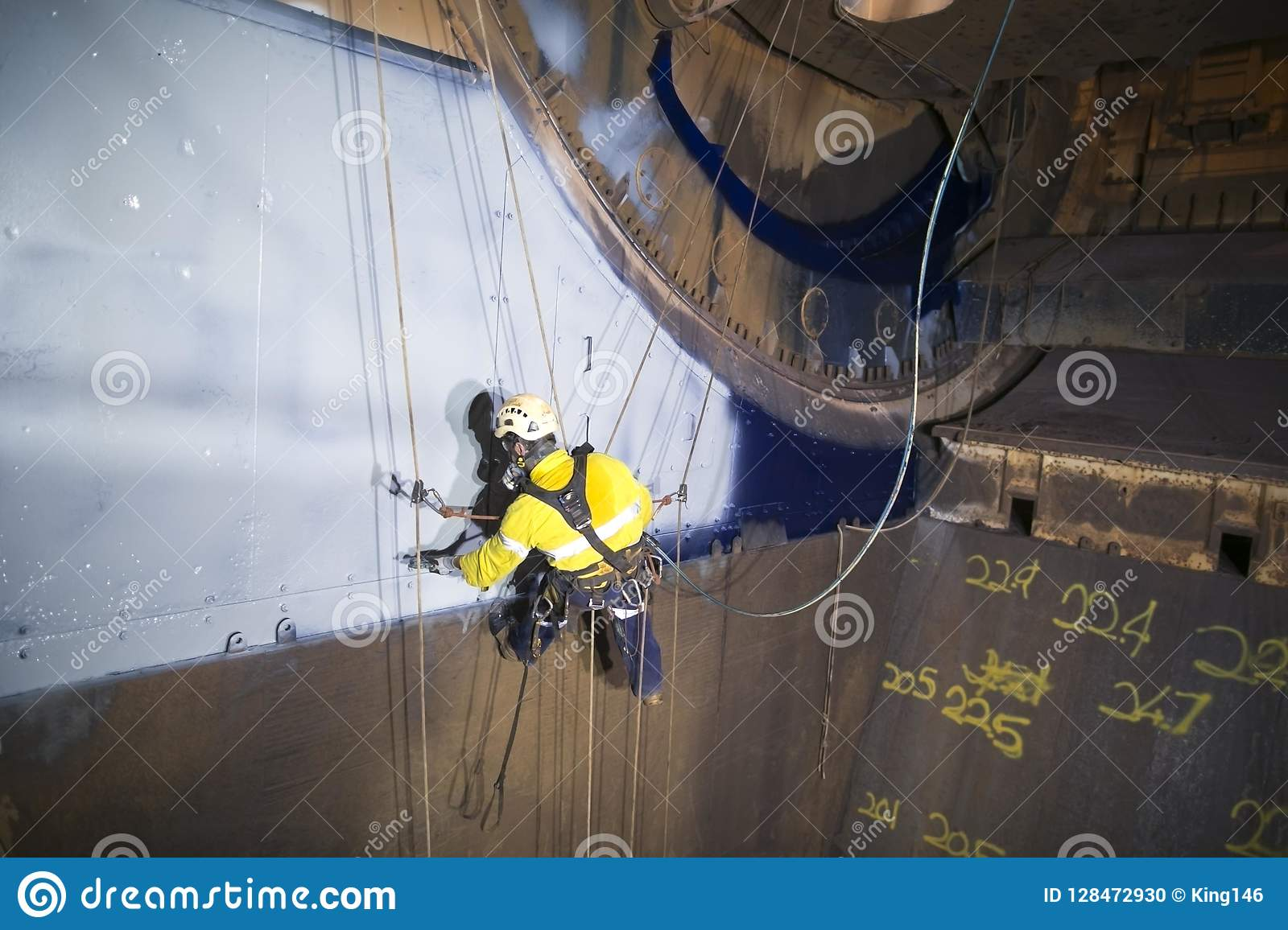 Male industrial rope access technician painter working at height hanging on twin ropes