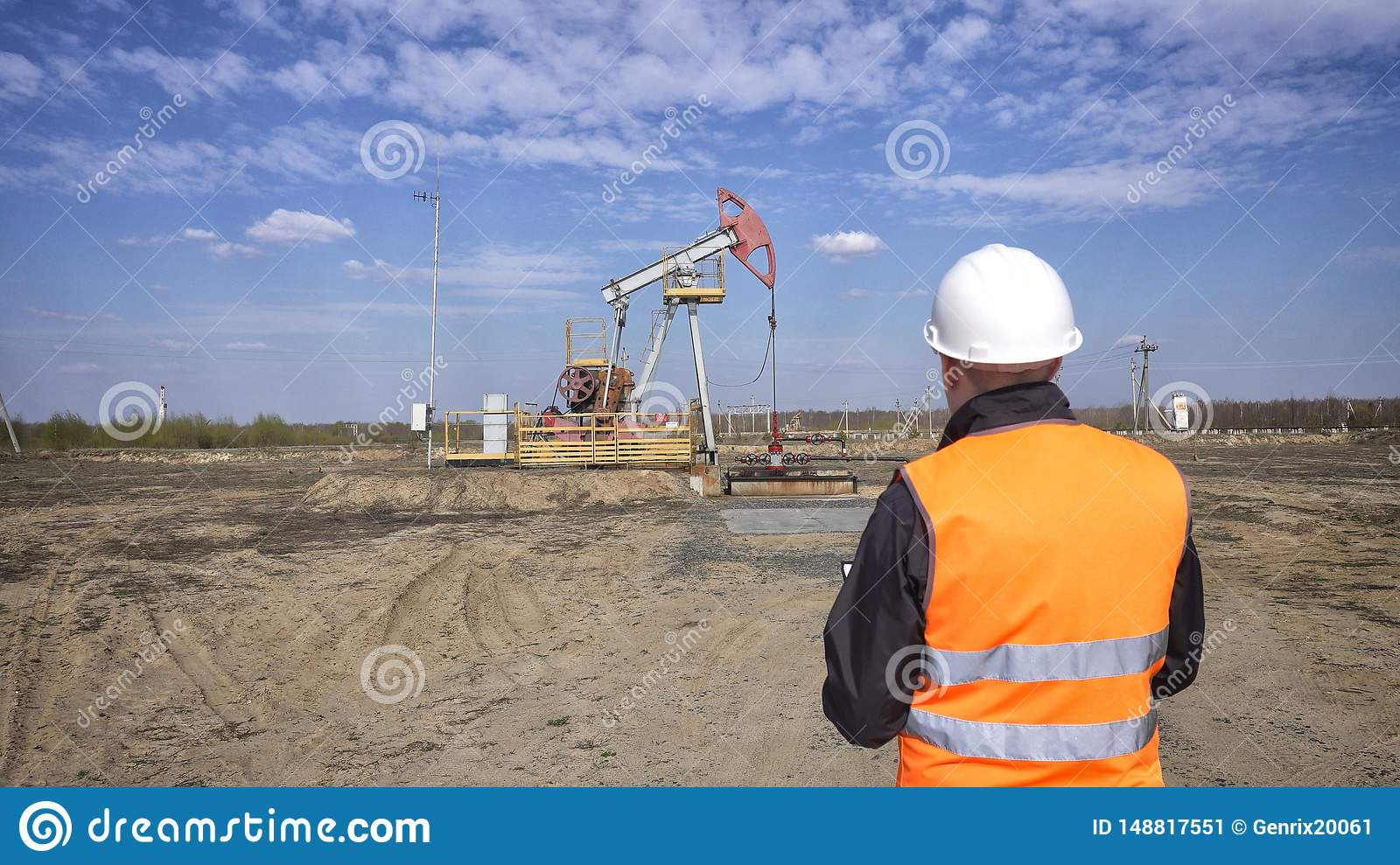 A male inspector-operator in a signal vest and a white helmet records the readings about the pumping unit oil, gas and combustible