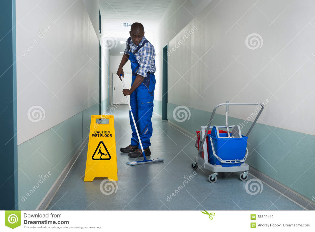 Male Worker With Broom Cleaning Office Corridor Stock