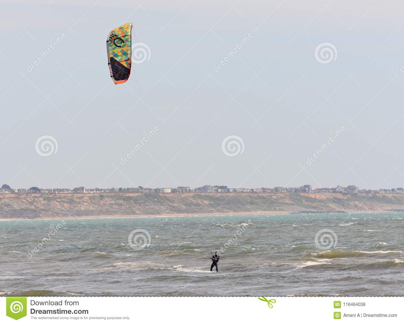 Recreational Water Sports Action. A Kiteboarder riding the waves. Dorset, UK. May 2018.