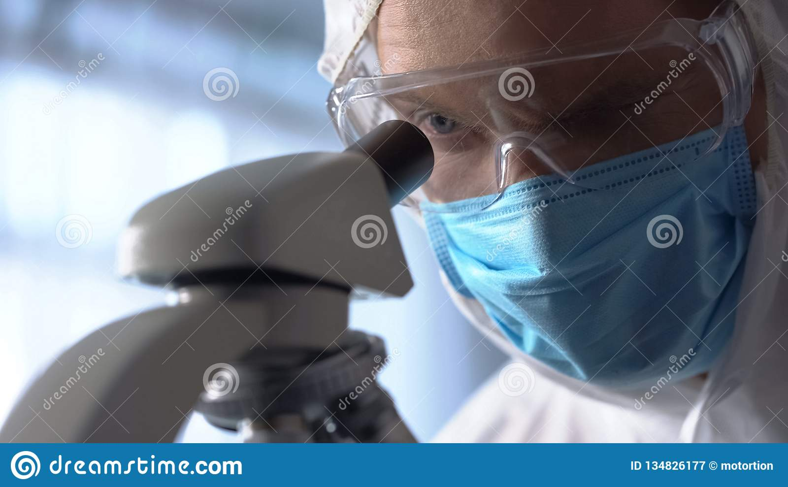 Male lab assistant in protective mask and eyewear using microscope for research