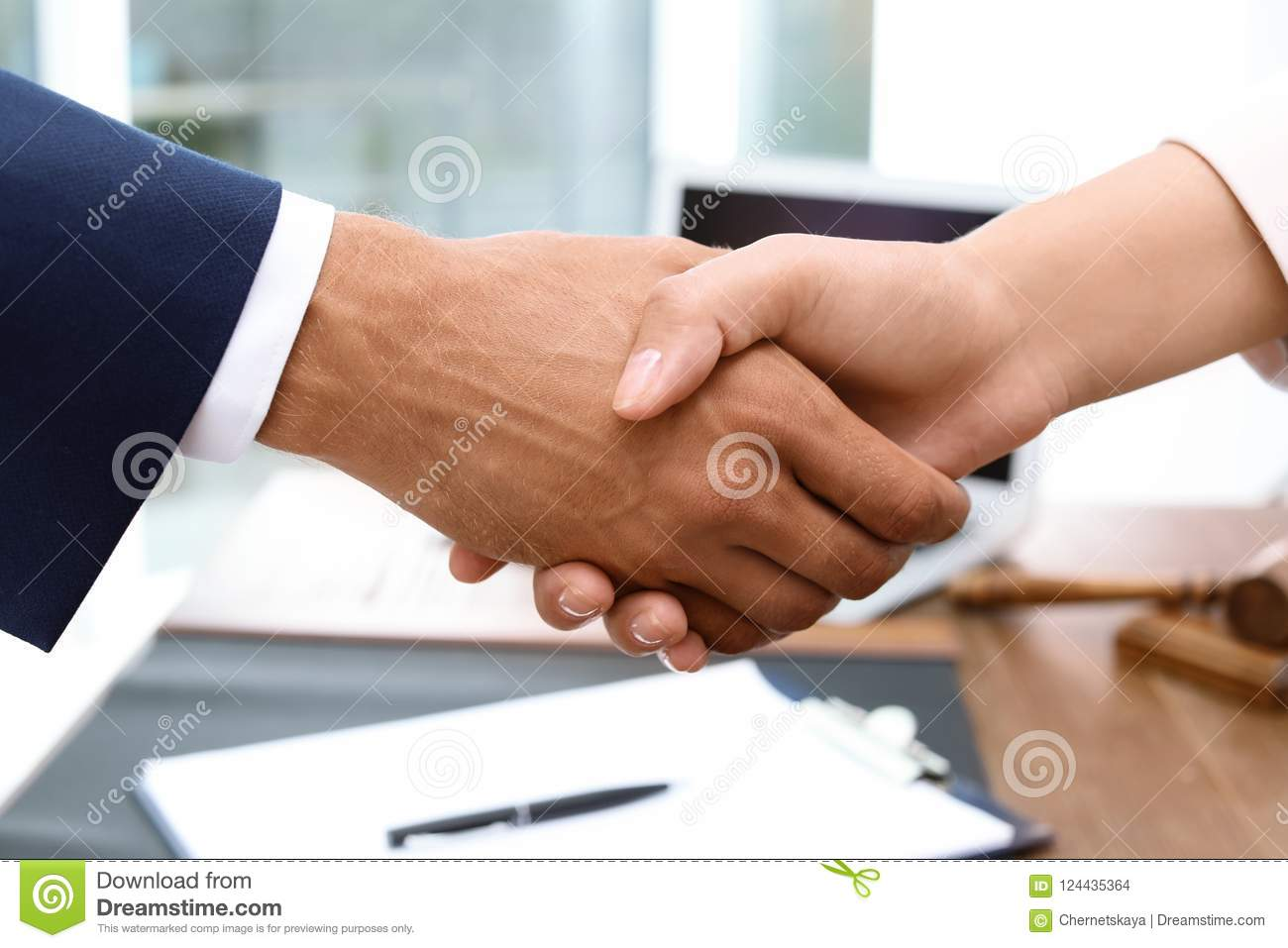 Male lawyer shaking hands with woman over table