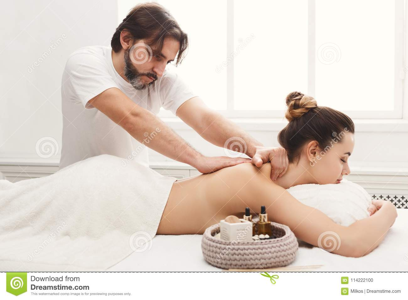Male masseur doing professional body massage