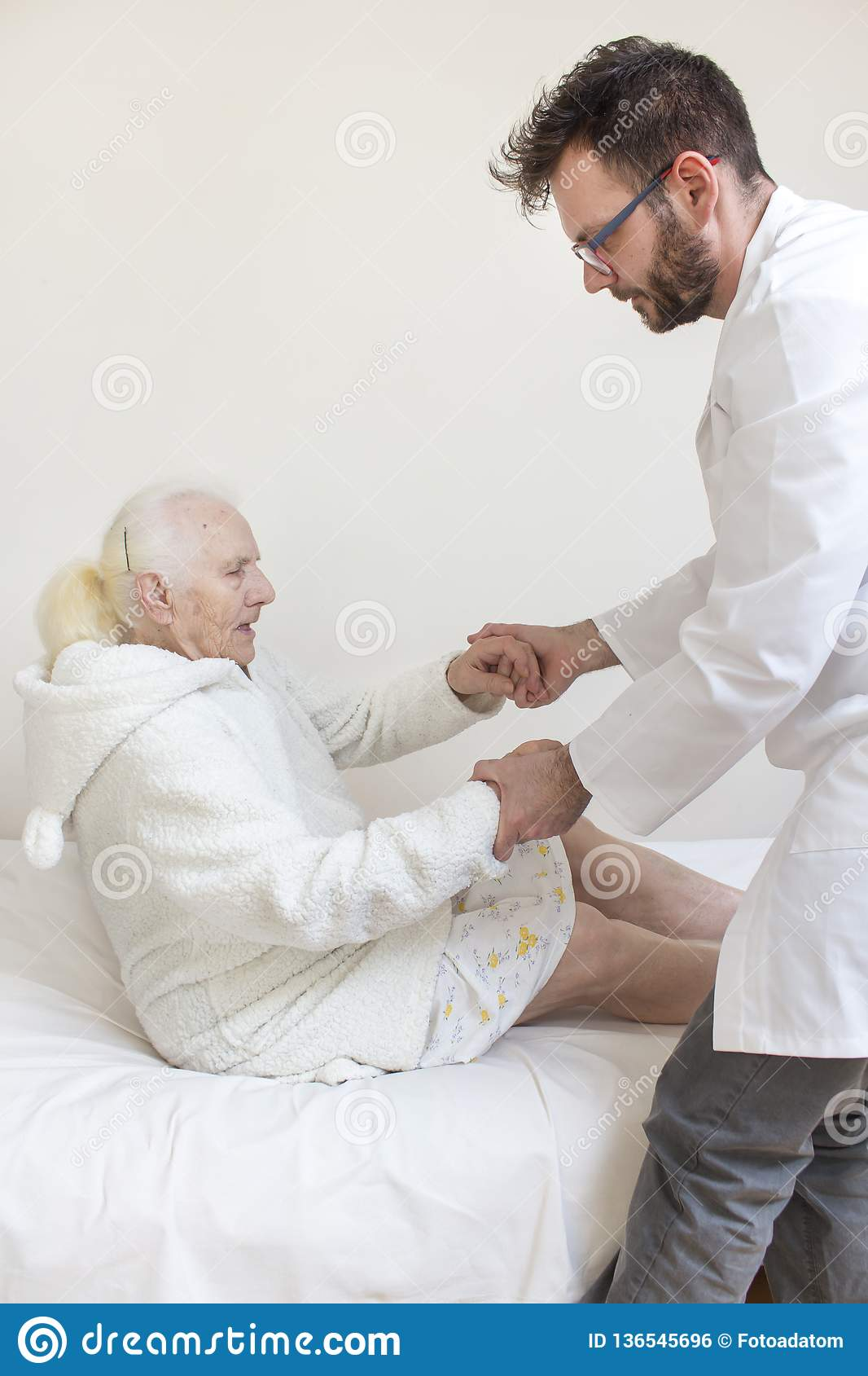 Male nurse helps to get up from the bed of an old woman.