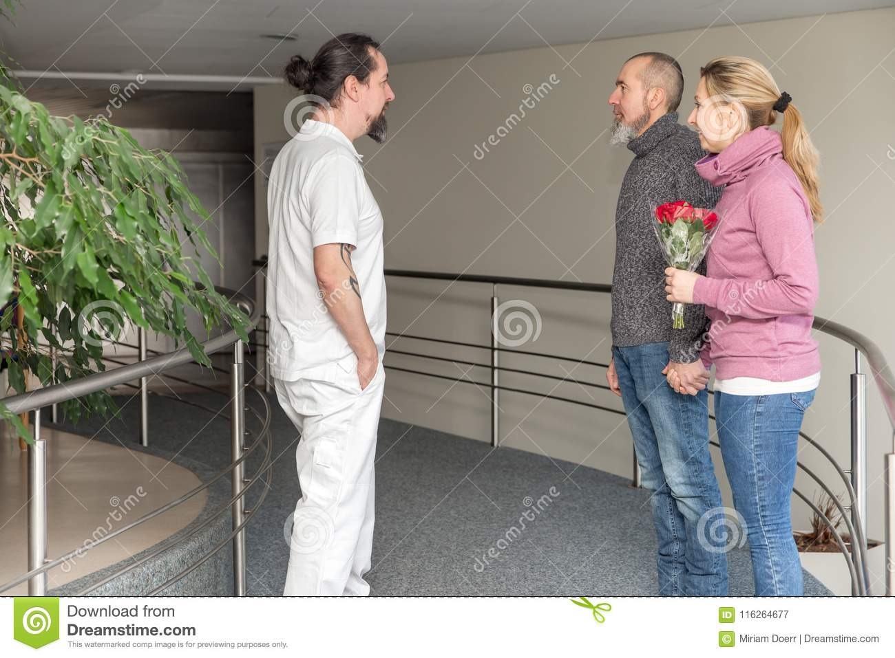 Male nurse with two visitors in a corridor