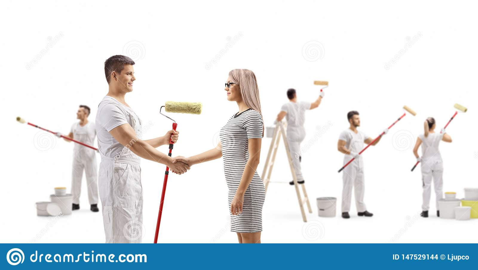 Male painter shaking hands with a young woman and workers painting wall