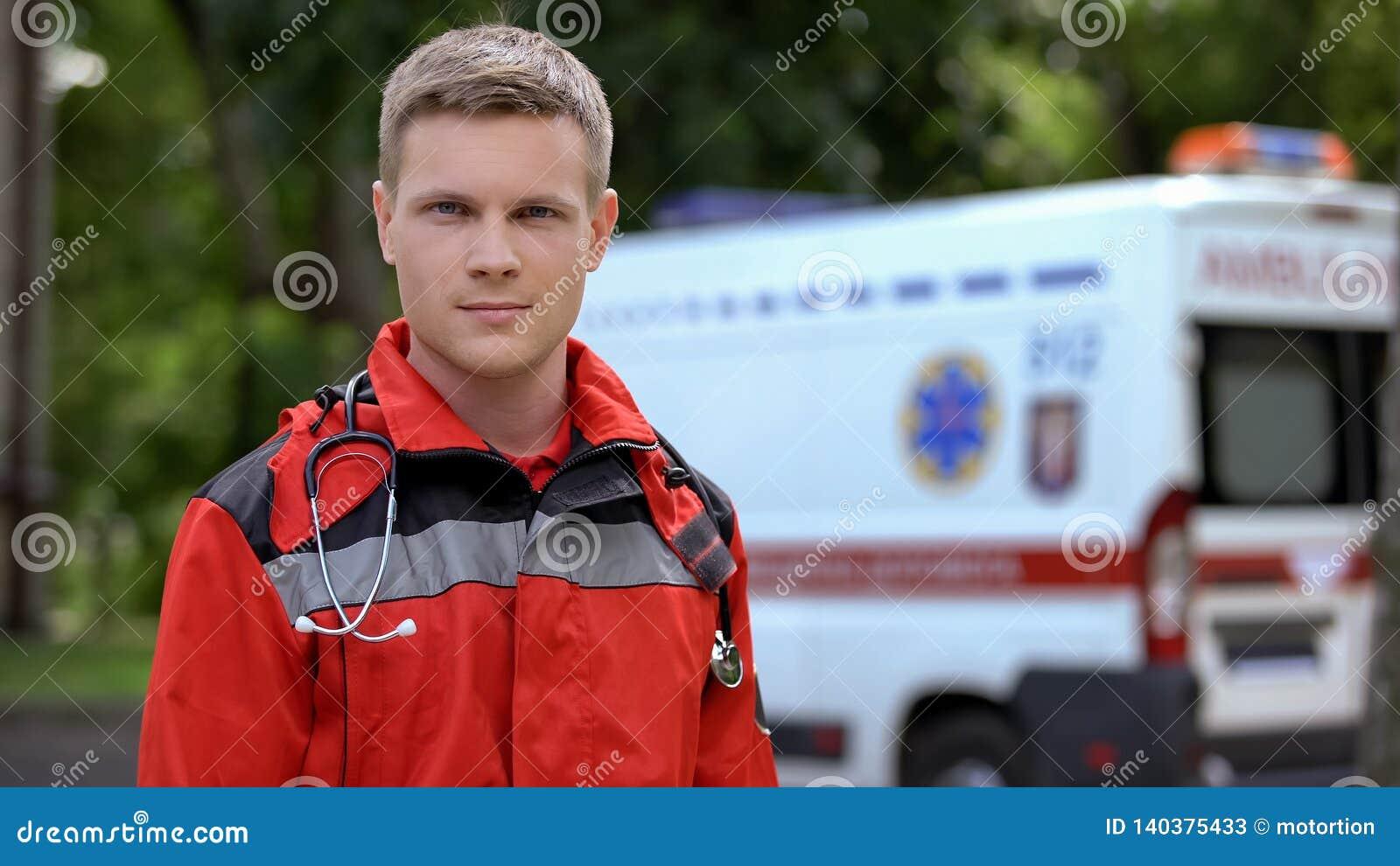 Male paramedic posing for camera, ambulance on background, professionalism