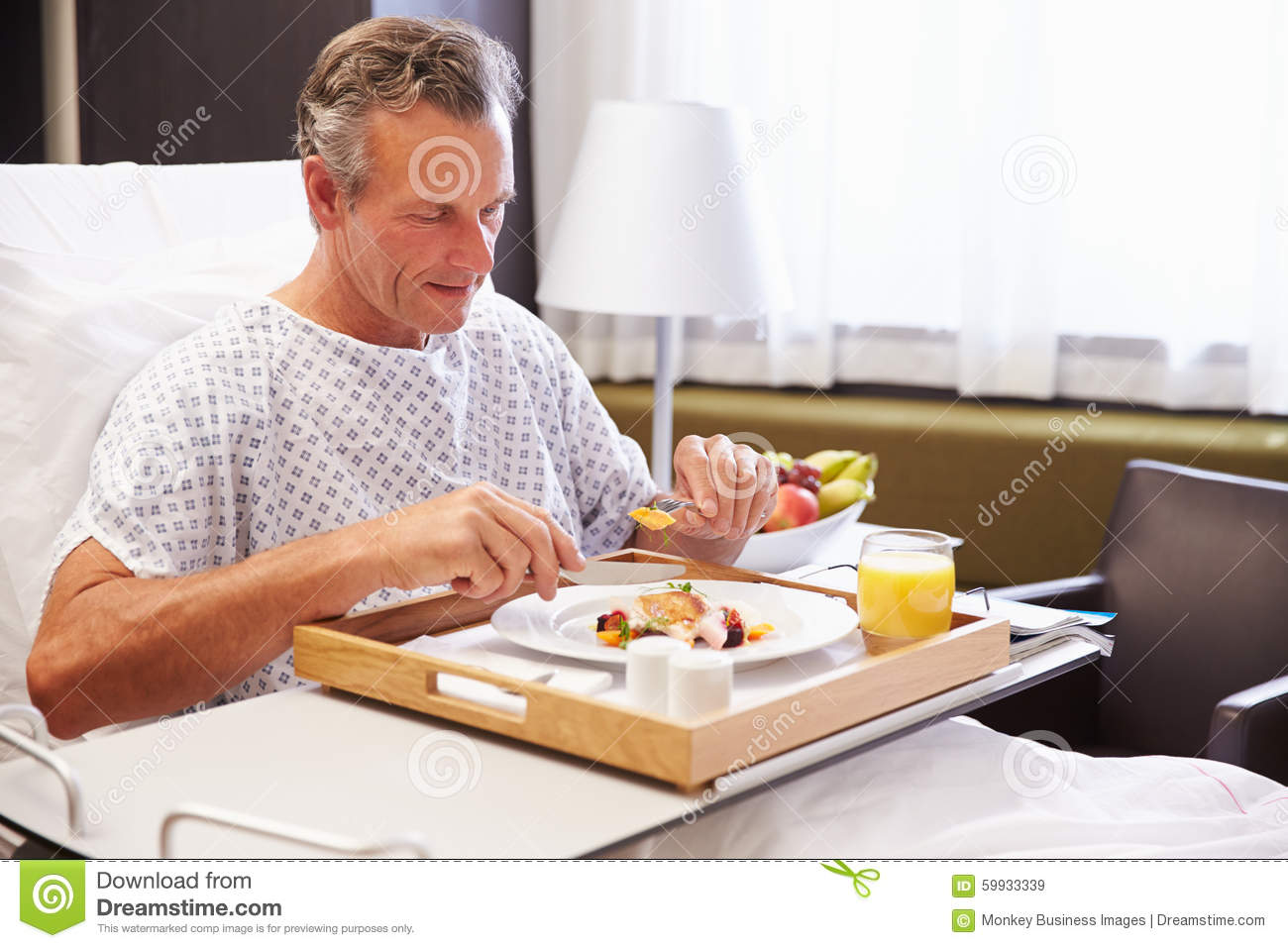 male patient in hospital bed eating meal from tray stock