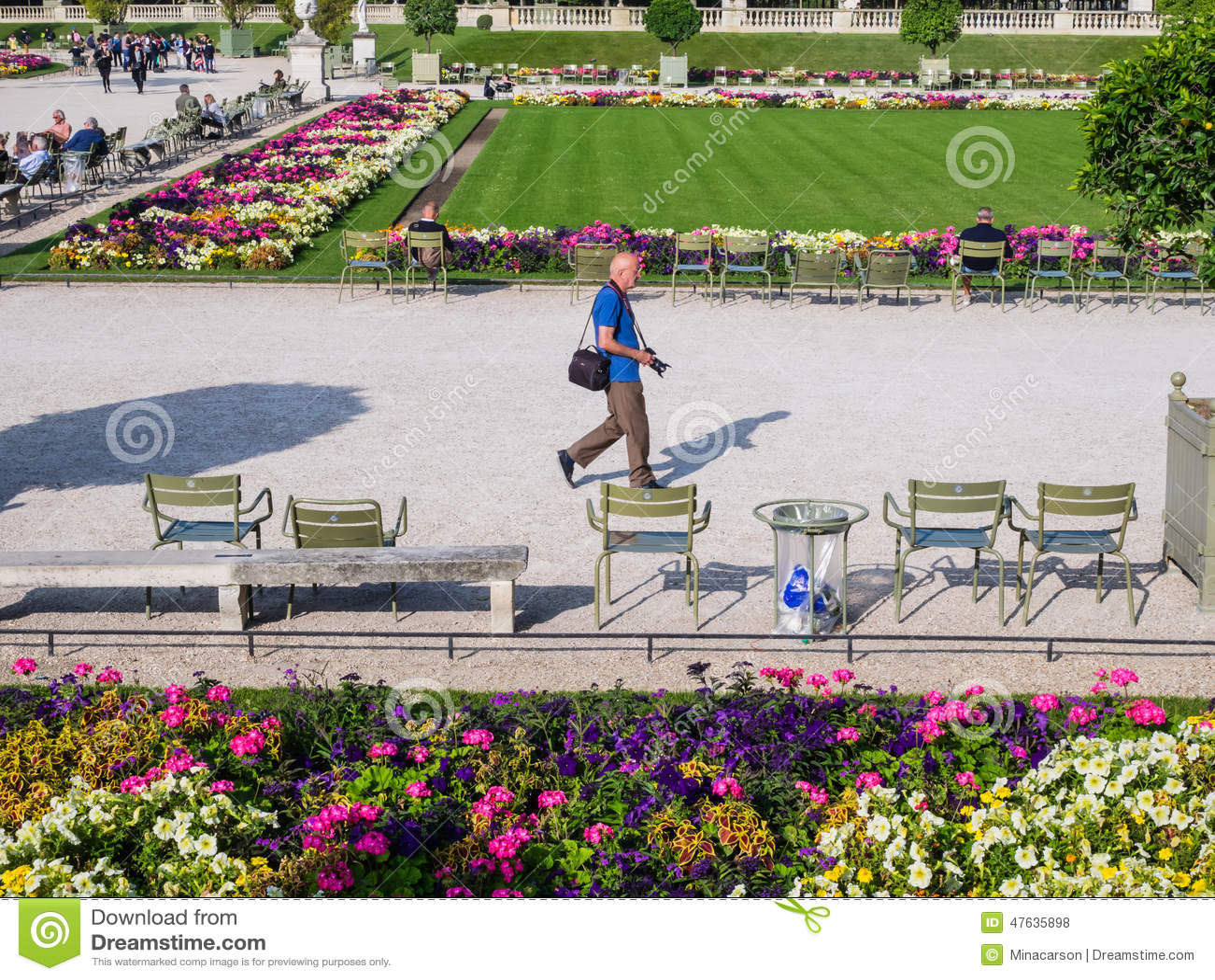 Male photographer strolls through Luxembourg Garden, paris, Fran