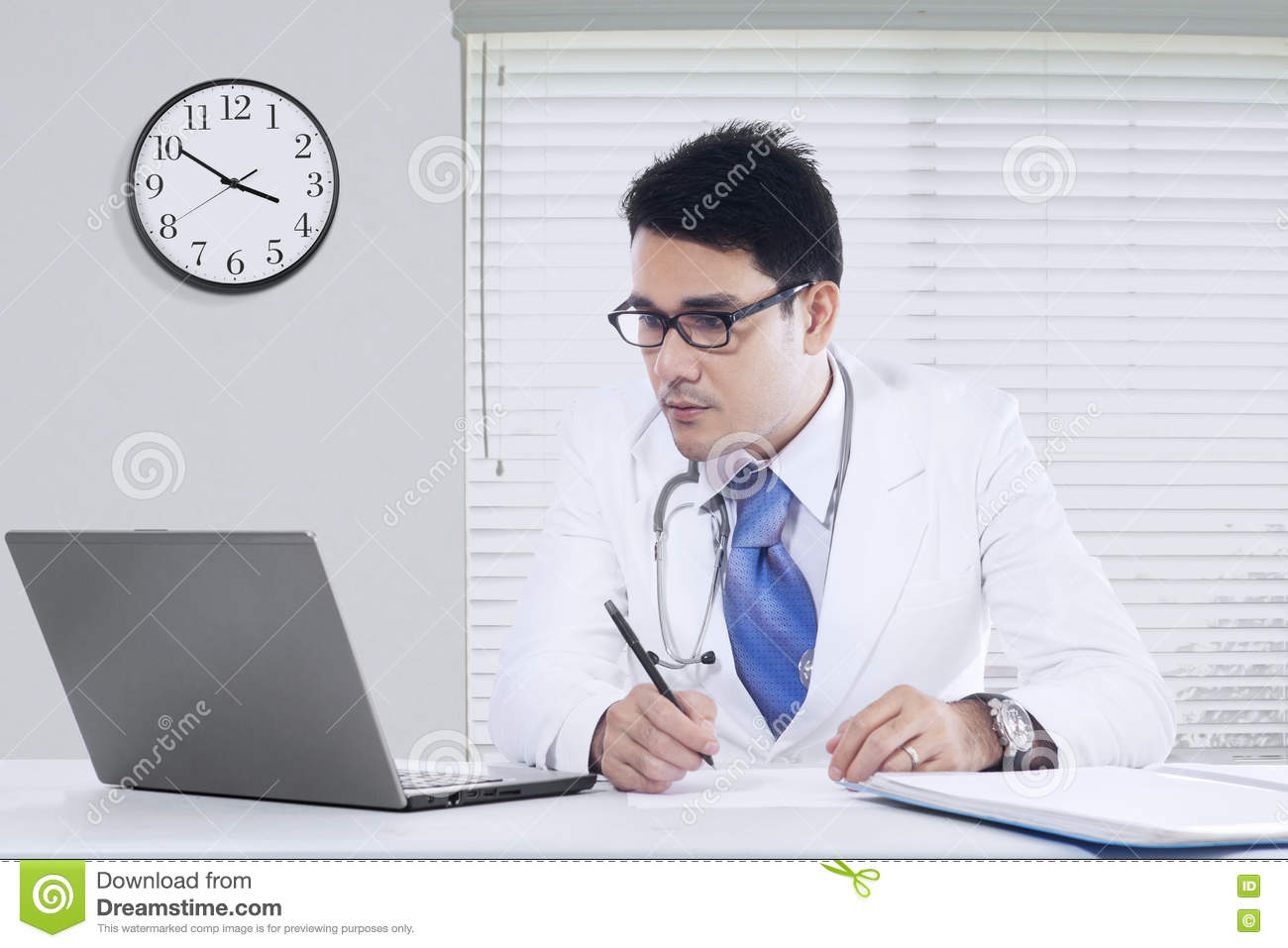6e5e7e4f1d1a Image of a male physician working in the office while writing a  prescription and looking at the laptop