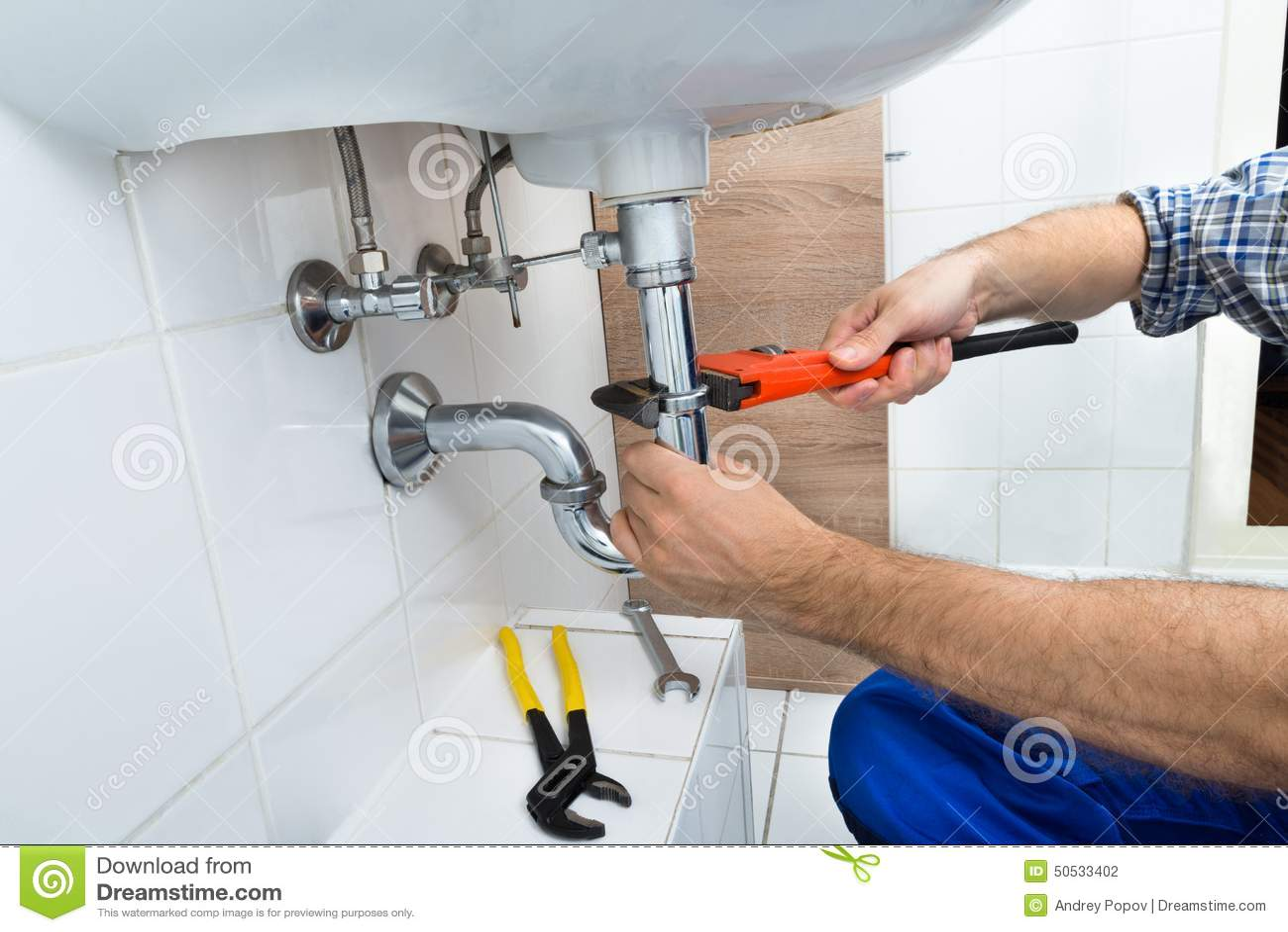 Male plumber fixing sink in bathroom stock photo image for Fixing bathroom sink