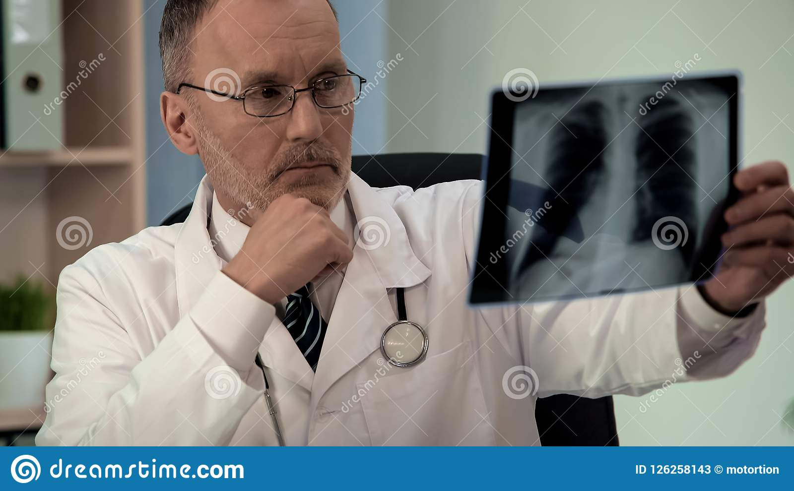 Male pulmonologist scrutinizing chest x-ray, looking for pathology, diagnostics