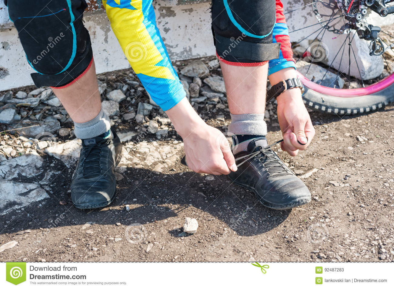Male racer mtb cyclist preparing for race tying shoelaces