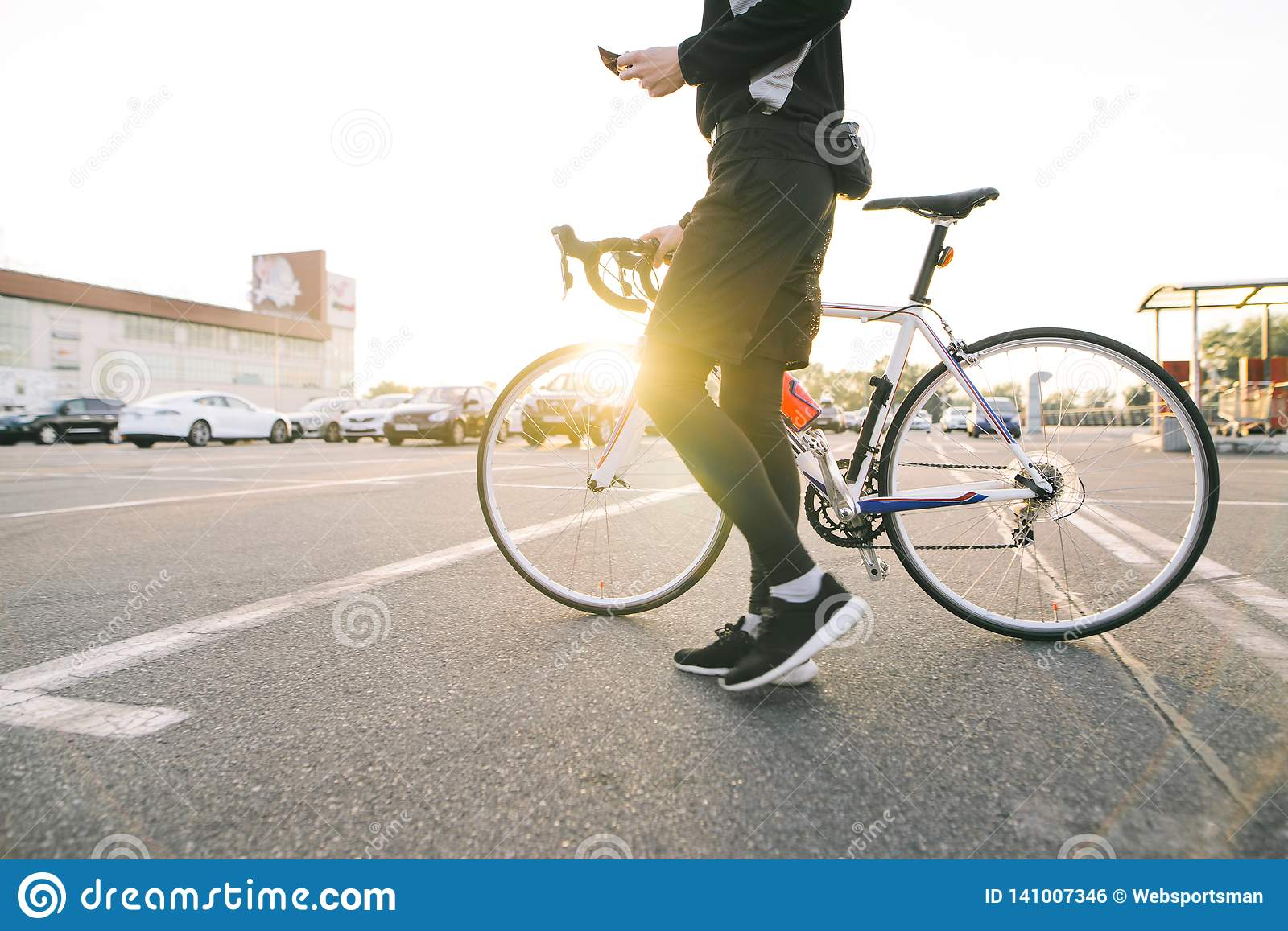 Male rider with a bicycle on the background of the sunset . Man cyclist rides a bike in the city