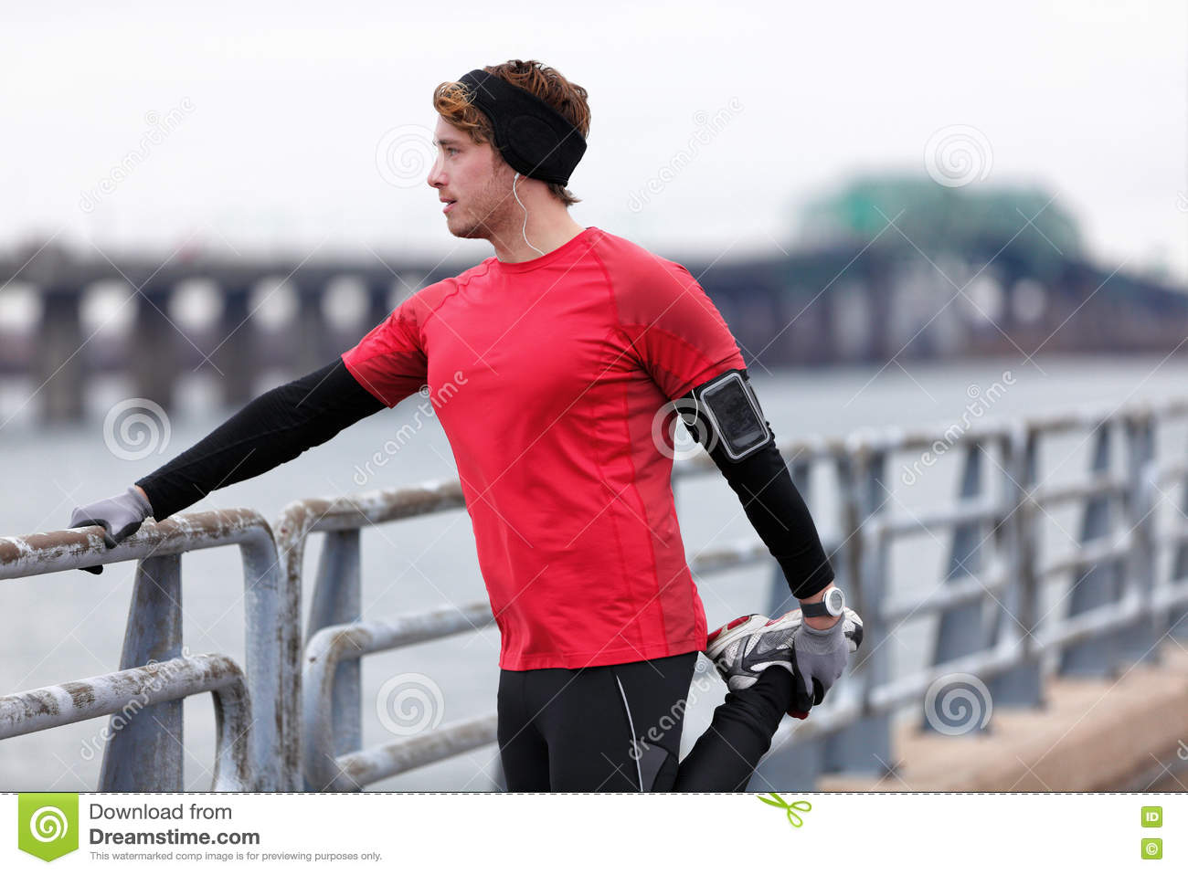 Male runner training in cold winter doing warm-up