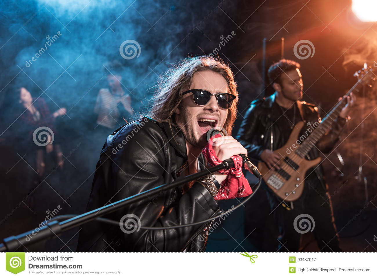 Male singer with microphone and rock and roll band performing hard rock music