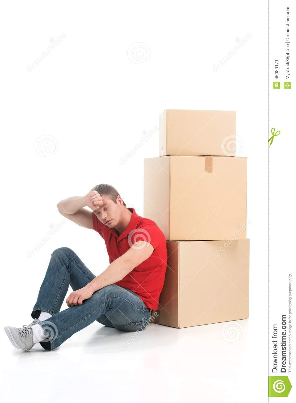 male sitting on floor tired of moving boxes  stock photo