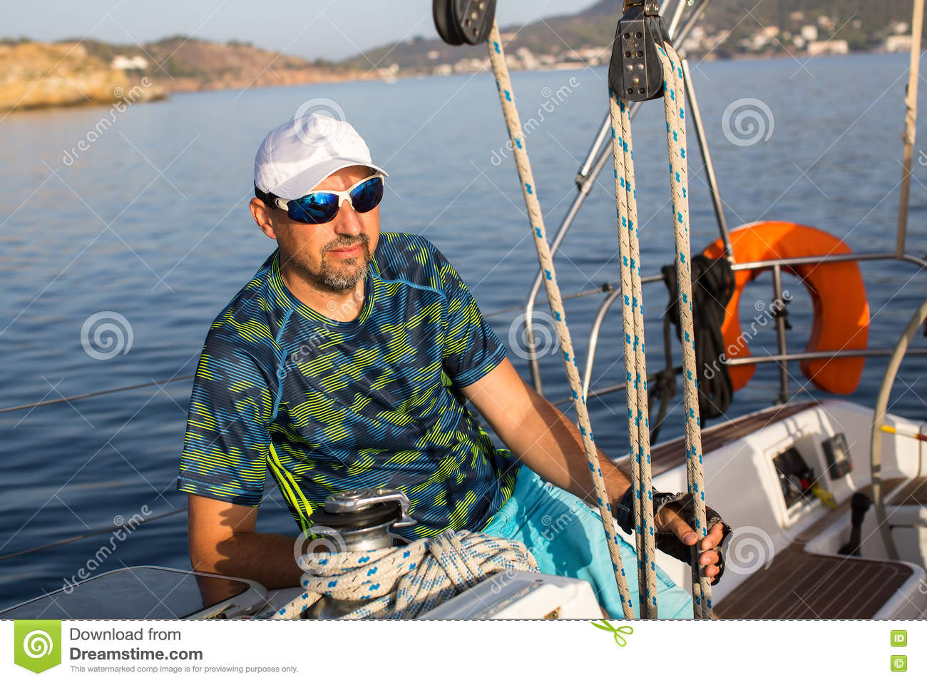 Male skipper sitting on his sailing yacht near the rigging. Sport.