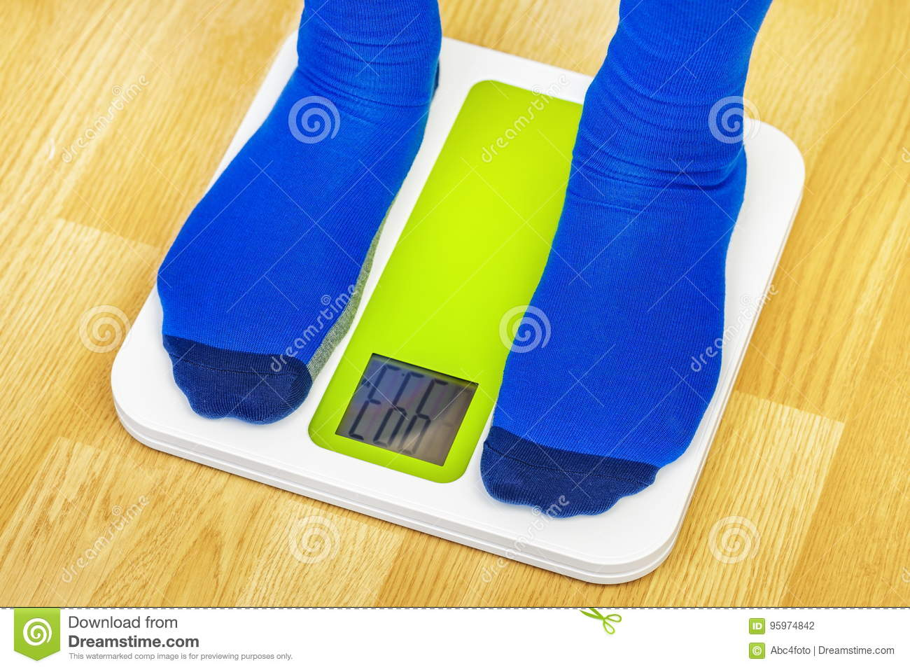 Male in socks with overweight standing on the scale