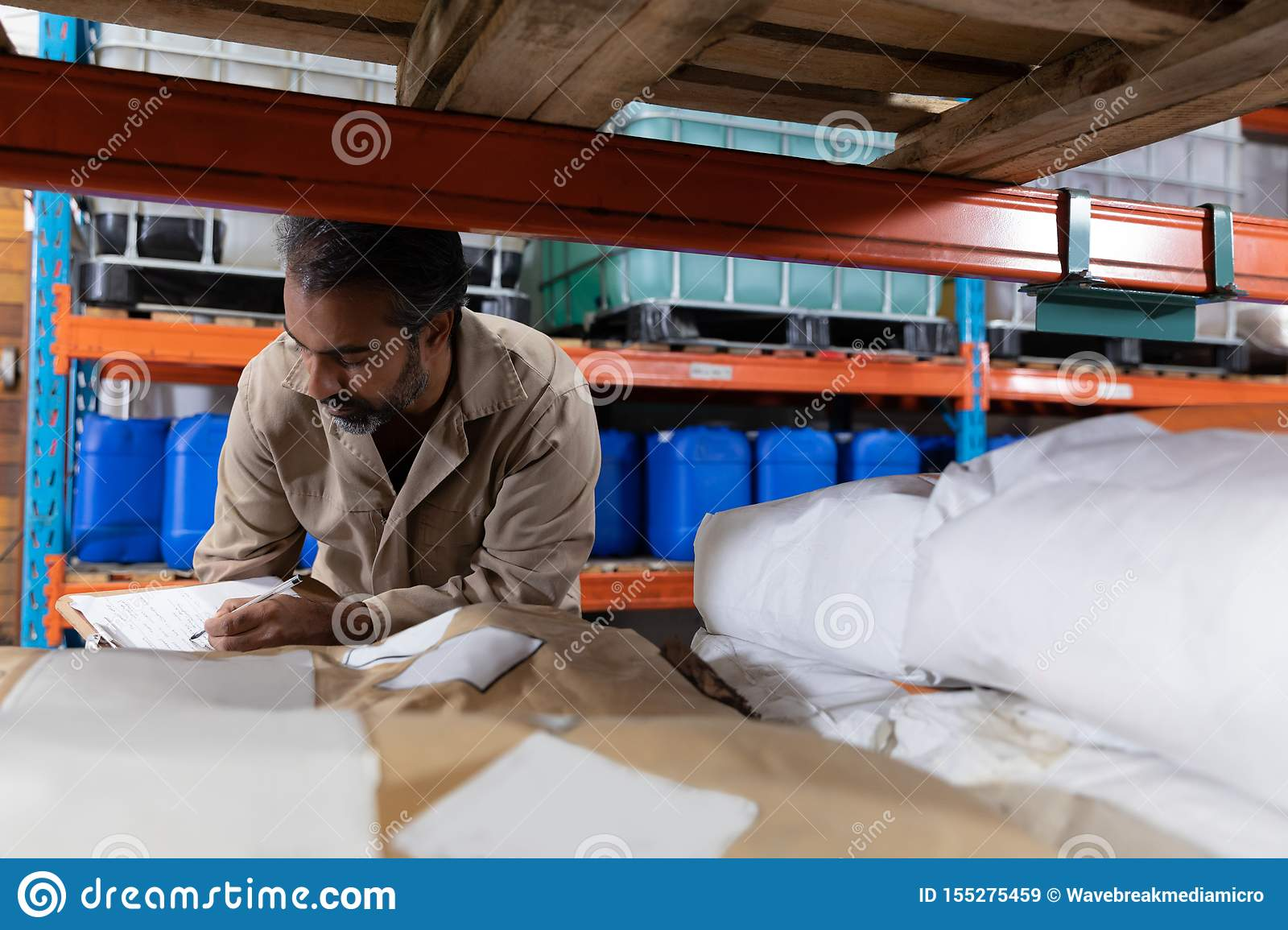 Male staff checking stocks in warehouse