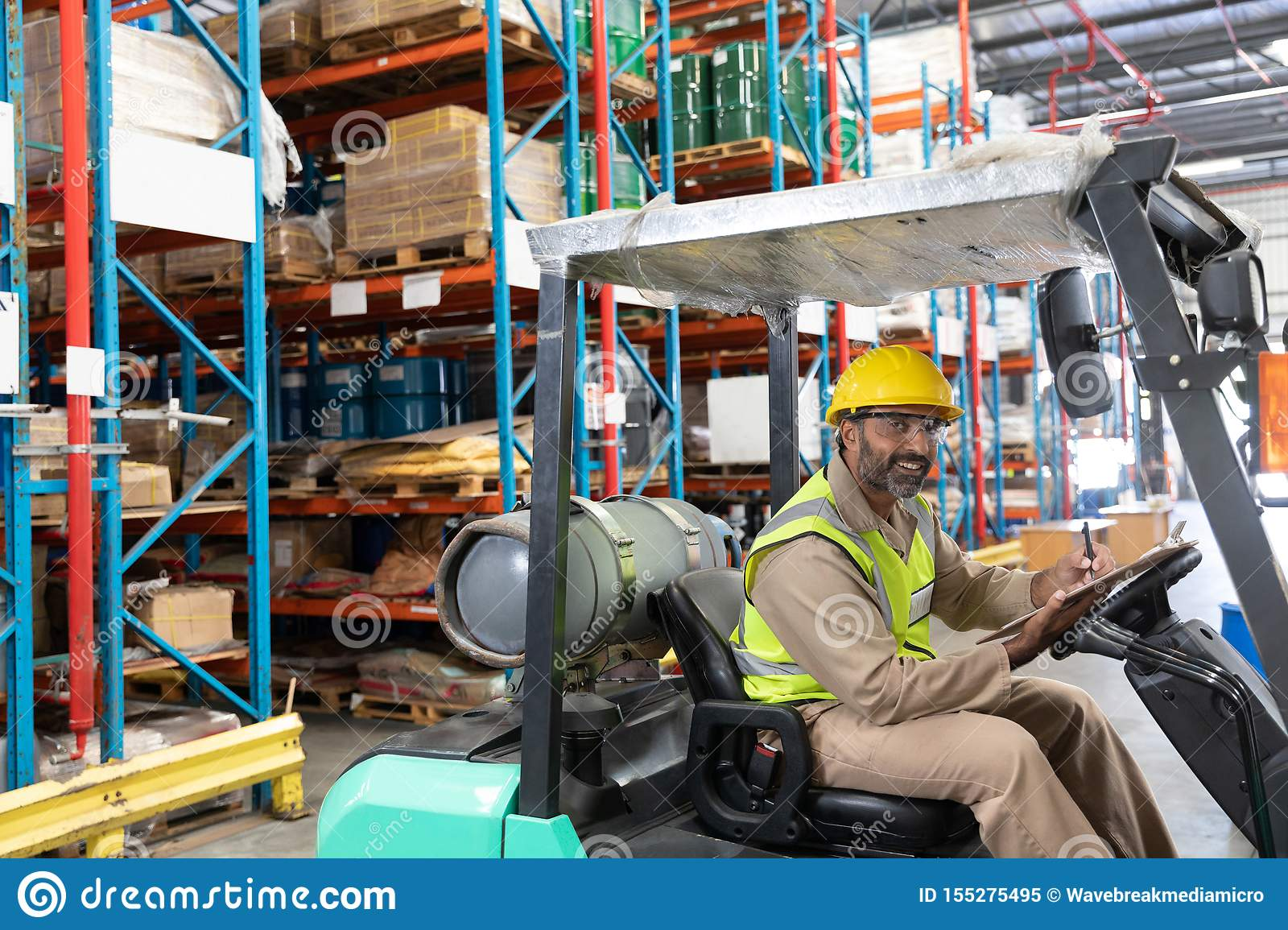Male staff writing on clipboard while sitting on forklift in warehouse