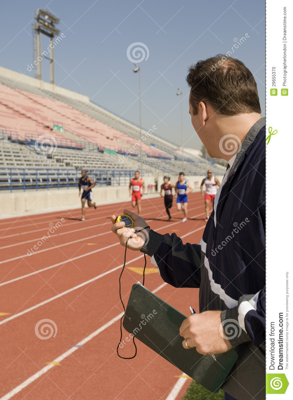 Male With Stopwatch Looking At Athletes Racing