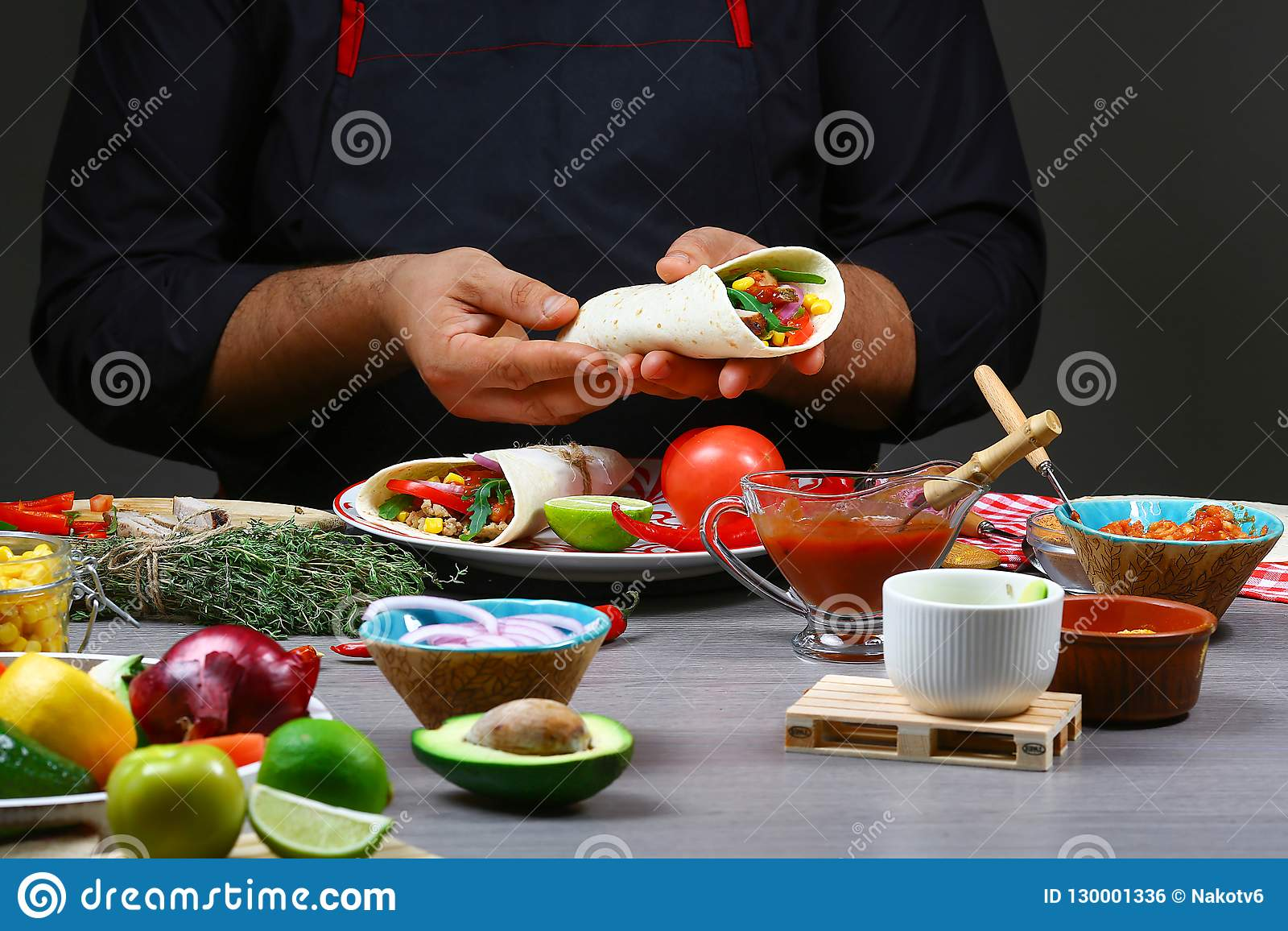 Male street vendor hands making taco. Mexican cuisine snacks, cooking fast food for commercial kitchen