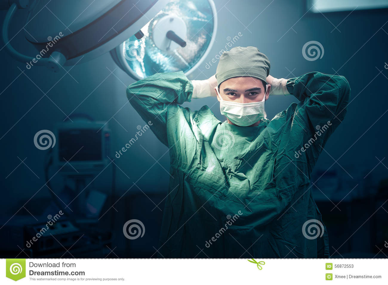 Male surgeon tying face mask at operating room