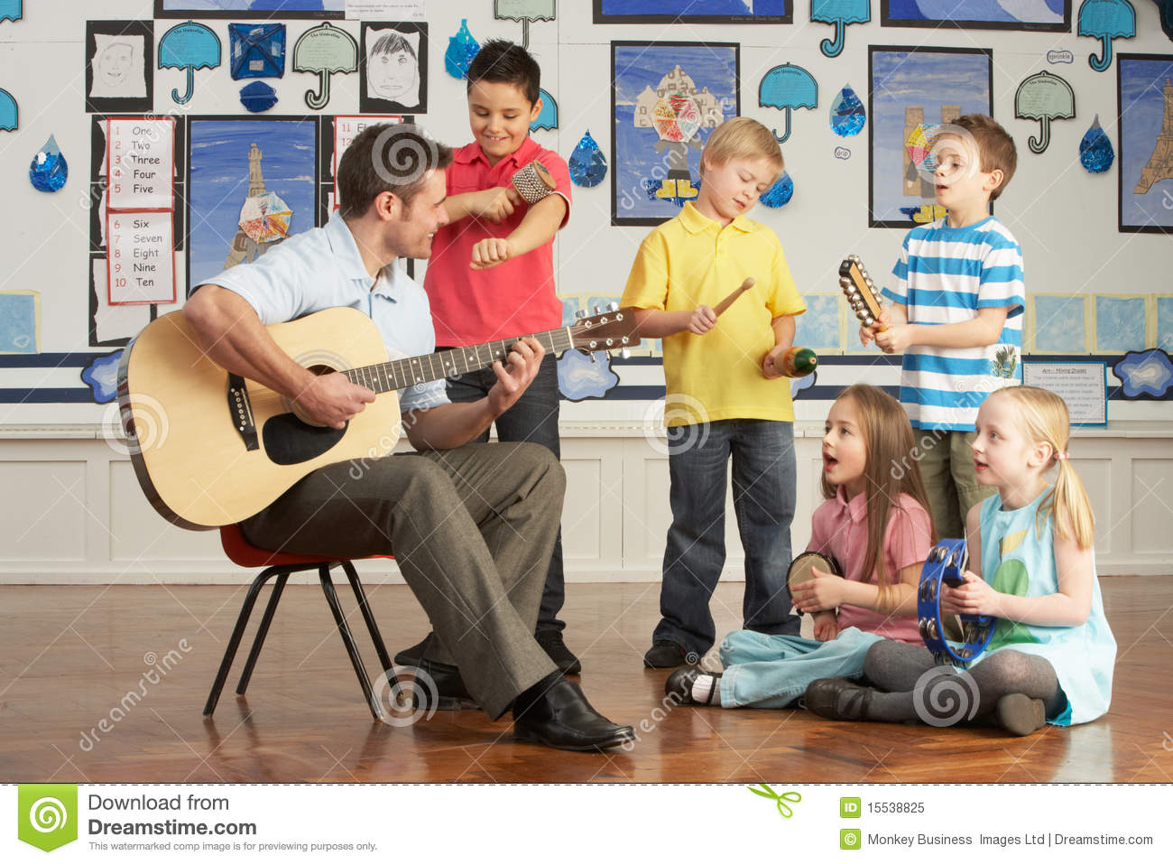 Male Teacher Playing Guitar With Pupils