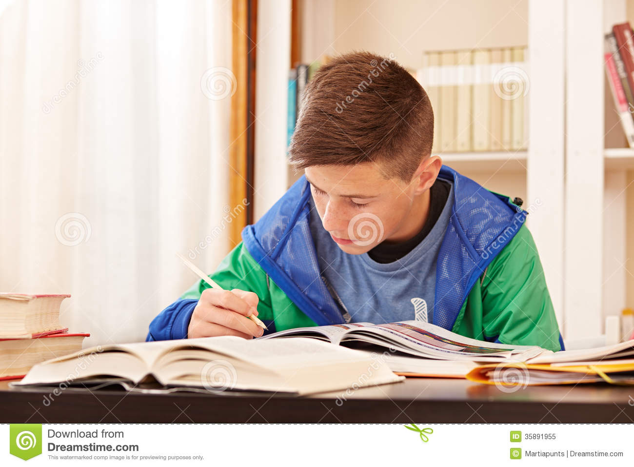 male teenager concentrated doing homework royalty free student writing at desk clipart student writing at desk clipart