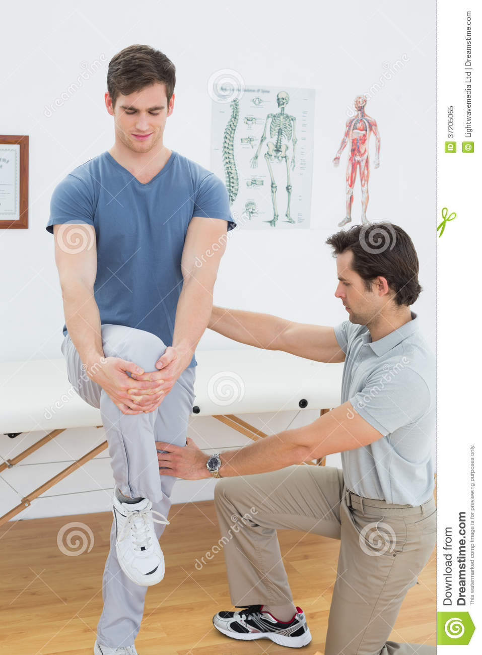 male therapist assisting man  stretching exercises royalty  stock photo image