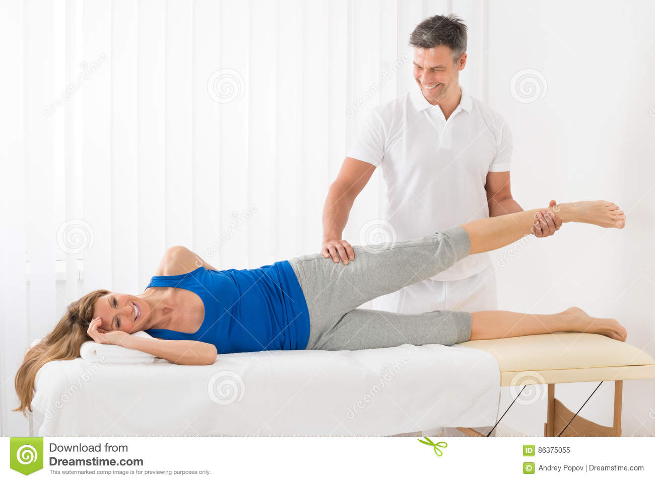 Happy Male Therapist Giving Leg Massage To Mature Woman