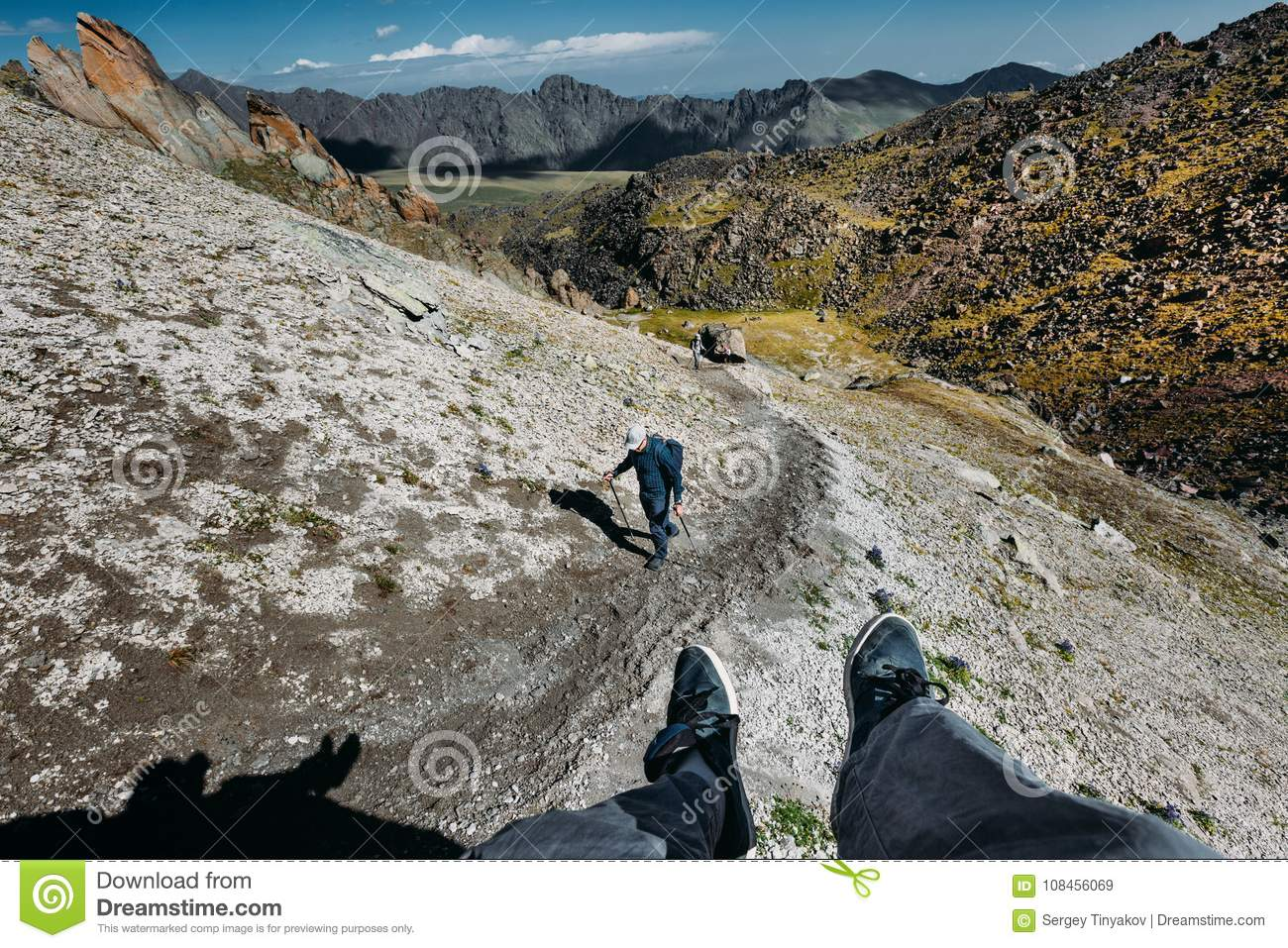 Male Traveler Sits On Top Mountain And Enjoys Mountain View In Summer. Group Of Tourists Climbs Uphill. Point Of View Shot