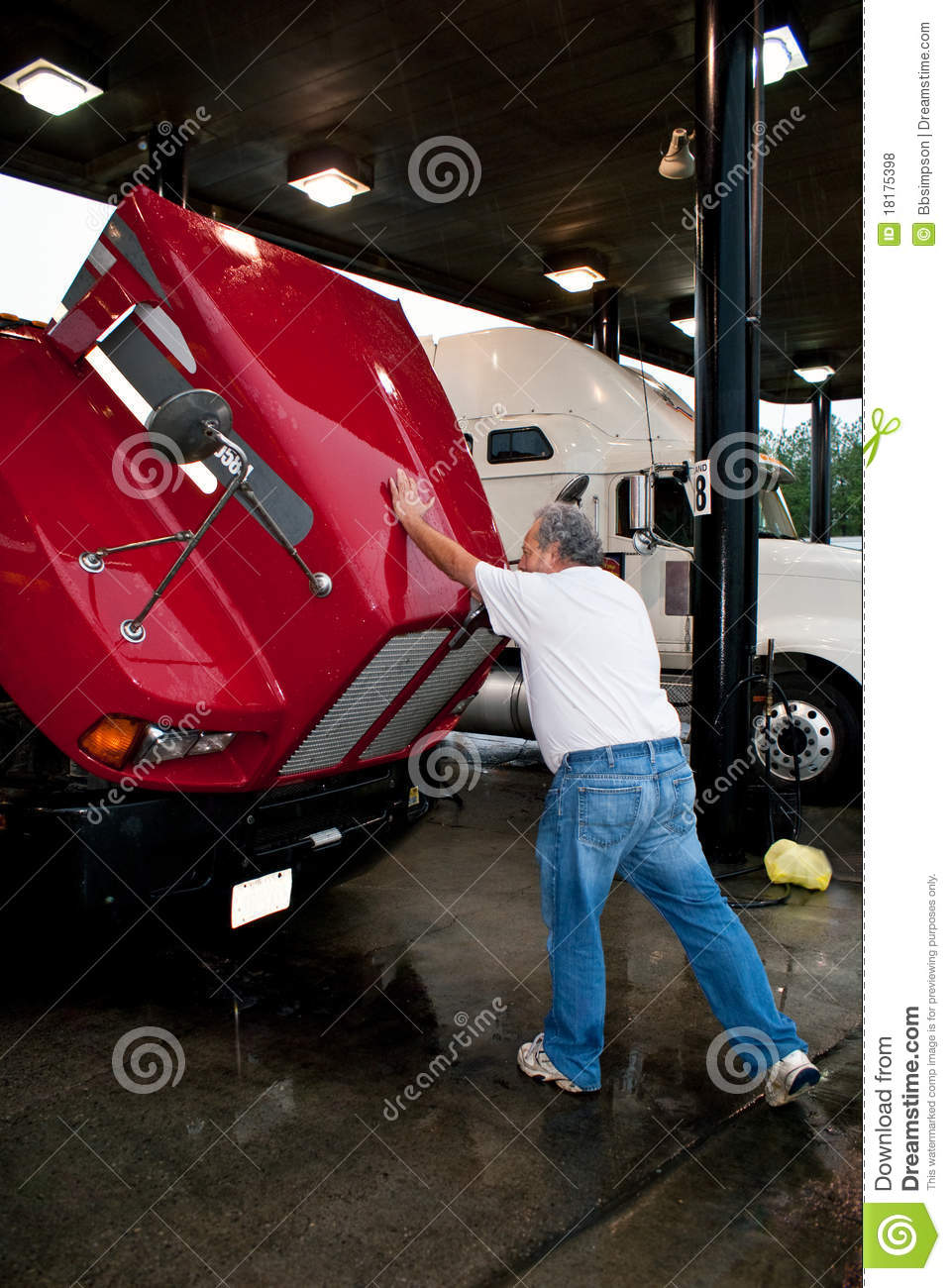 male truck driver closing hood of 18-wheeler royalty free stock photos