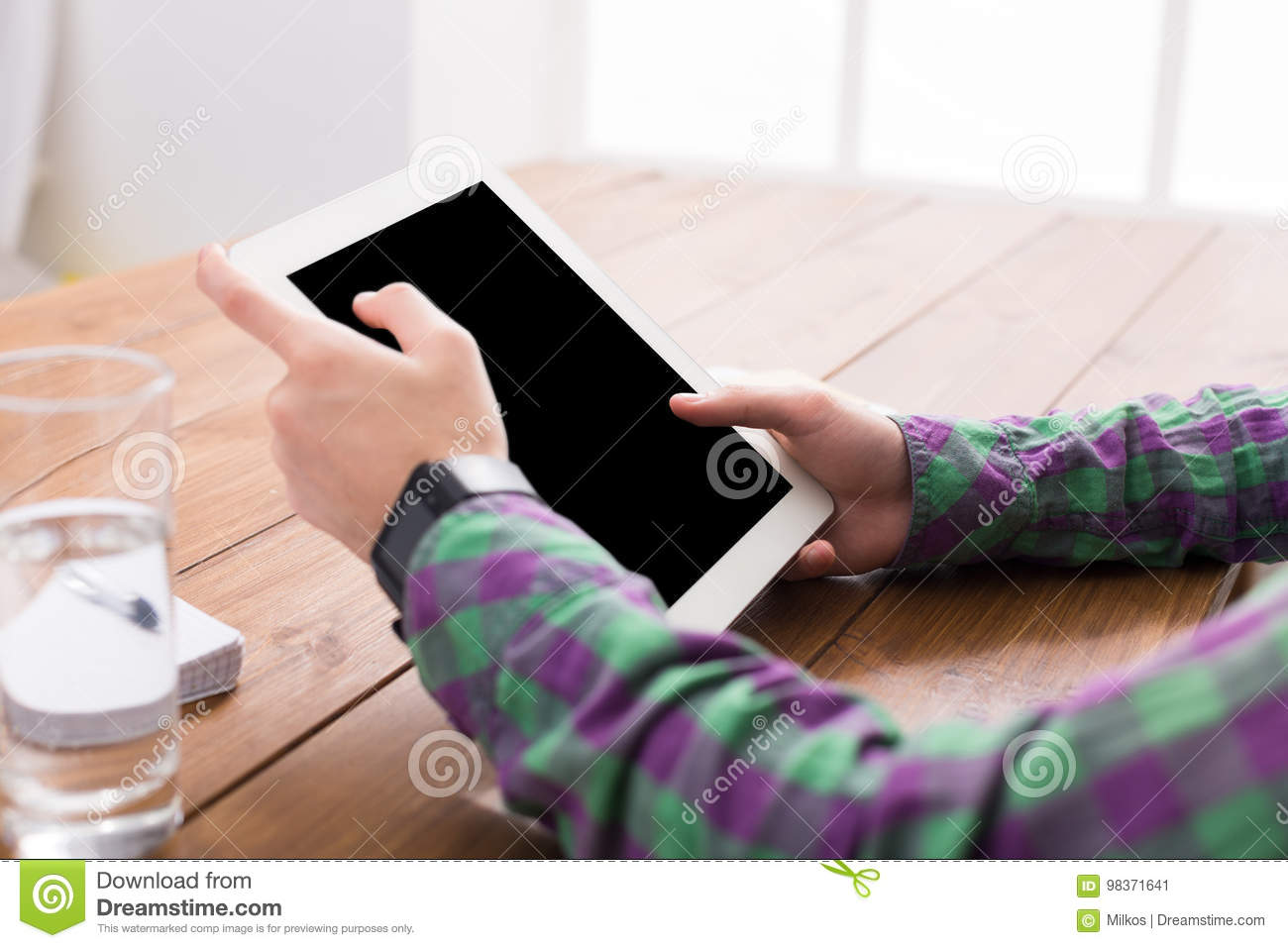 Male using digital tablet, close up, side view,