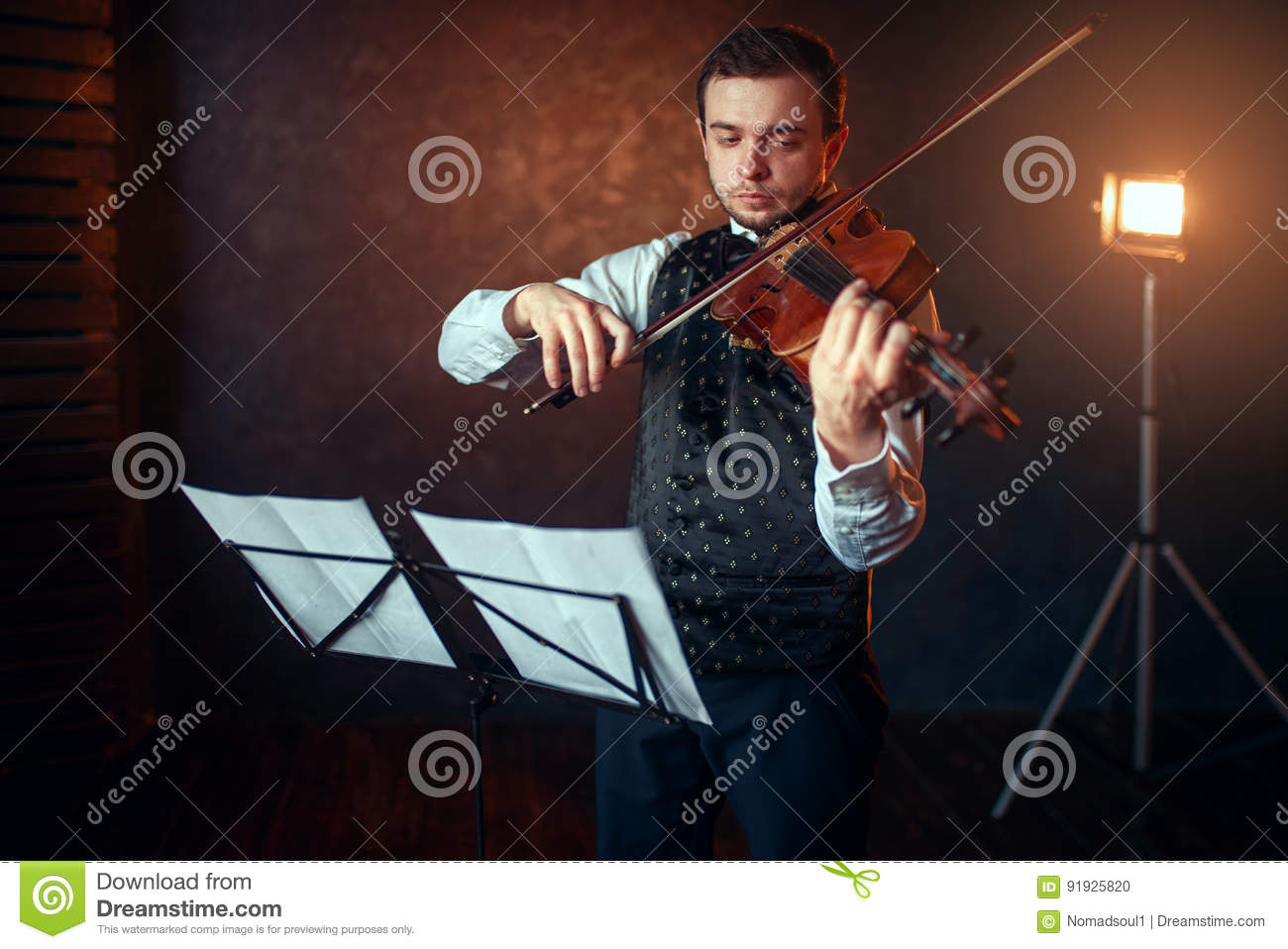 Male Violinist With Violin Against Music Stand Stock Photo