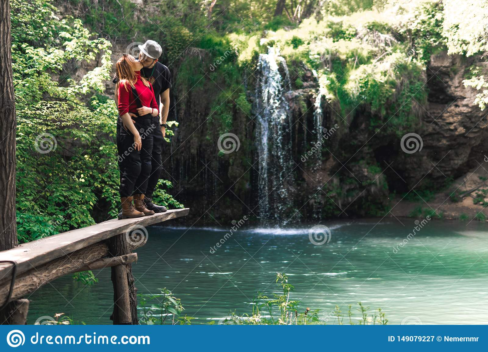 Male and woman, happy couples motorcyclists travelers. travel nature Forests, mountains, beautiful waterfall on background. summer