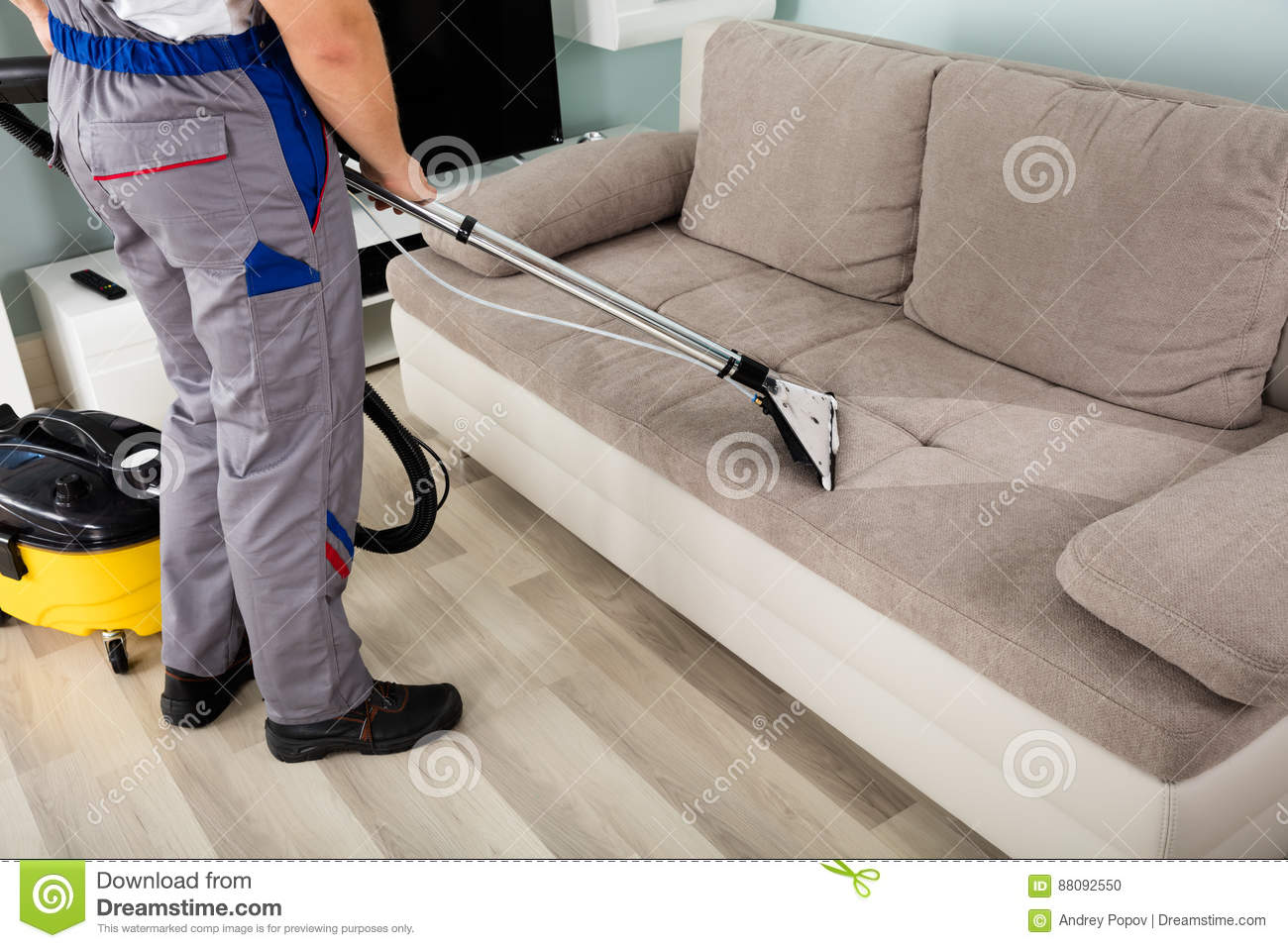 Male Worker Cleaning Sofa With Vacuum Cleaner Stock Photo