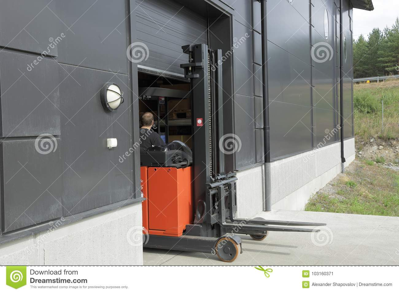 Male worker driving out of a warehouse on the fork-lift-truck