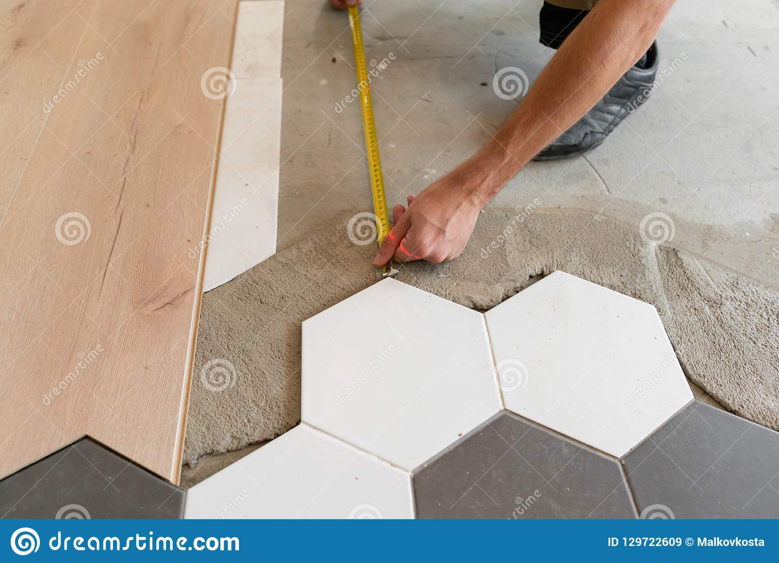 Male Worker Installing New Wooden Laminate Flooring On A Warm Film
