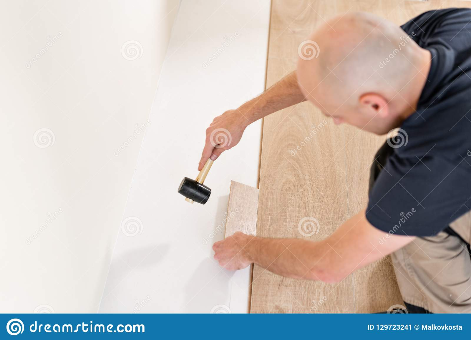 Male worker installing new wooden laminate flooring on a warm film foil floor. infrared floor heating system under